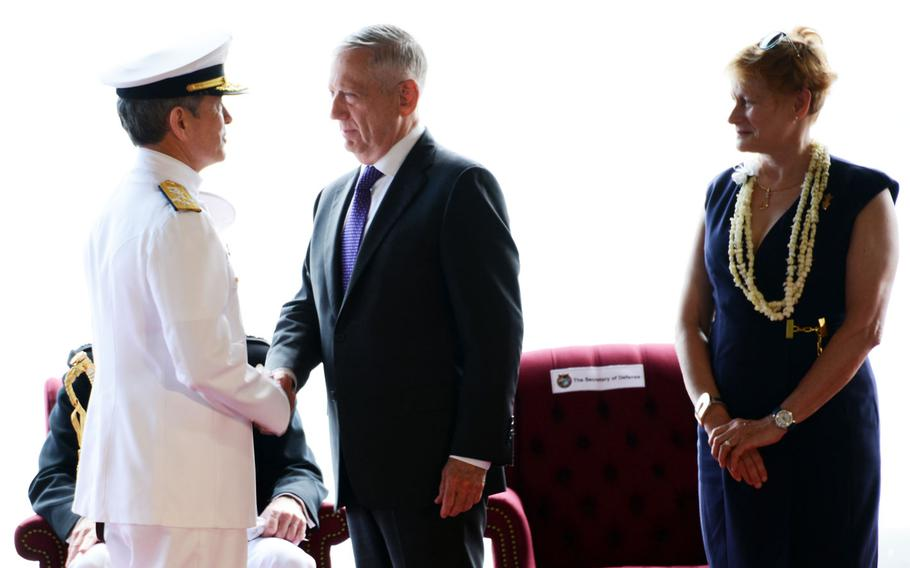 Secretary of Defense James Mattis bids farewell to the retiring Adm. Harry Harris during a change-of-command ceremony at Joint Base Pearl Harbor-Hickam, Hawaii, May 30, 2018. Watching is Harris's wife, Brunhilde 'Bruni' Bradley.