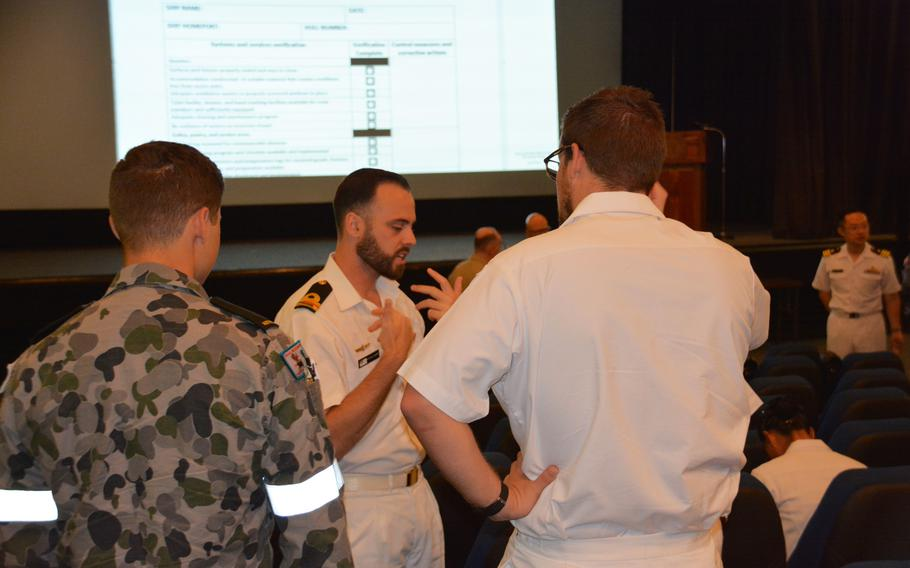 Medical personnel chat during a break at Joint Base Pearl Harbor-Hickam July 6 during a break in a two-day symposium held as part of the Rim of the Pacific exercise.