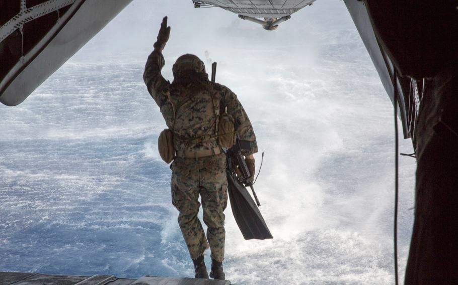 A U.S. Marine with the 3rd Reconnaissance Battalion jumps from a CH-53E Super Stallion helicopter July 2, 2018, during amphibious drills as part of Rim of the Pacific exercise on Marine Corps Base Hawaii.