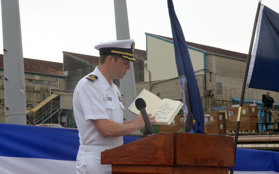 Cmdr. Micah Murphy, commanding officer of the USS John S. McCain, holds a signed copy of one of John McCain III's books.