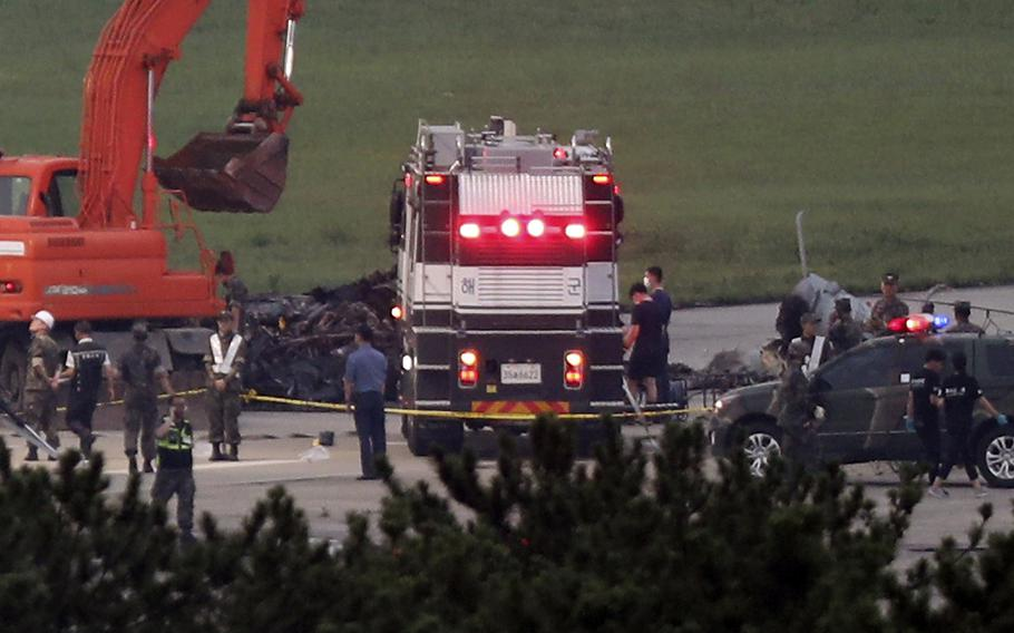 South Korean officials inspect a runway at an airport in Pohang, South Korea, where five people were killed Tuesday, July 17, 2018, in a helicopter crash, the Defense Ministry said.