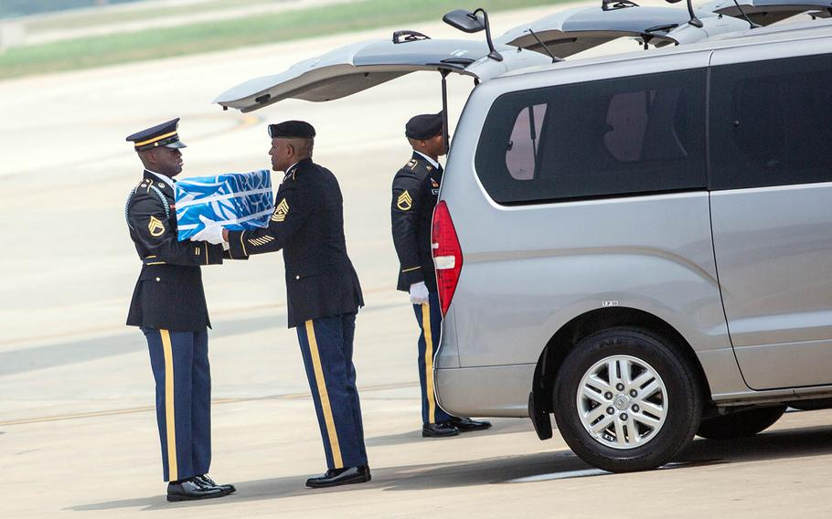 Staff Sgt. Jamil Green, left, hands over the final case of remains at Osan Air Base, South Korea, Friday, July 27, 2018.
