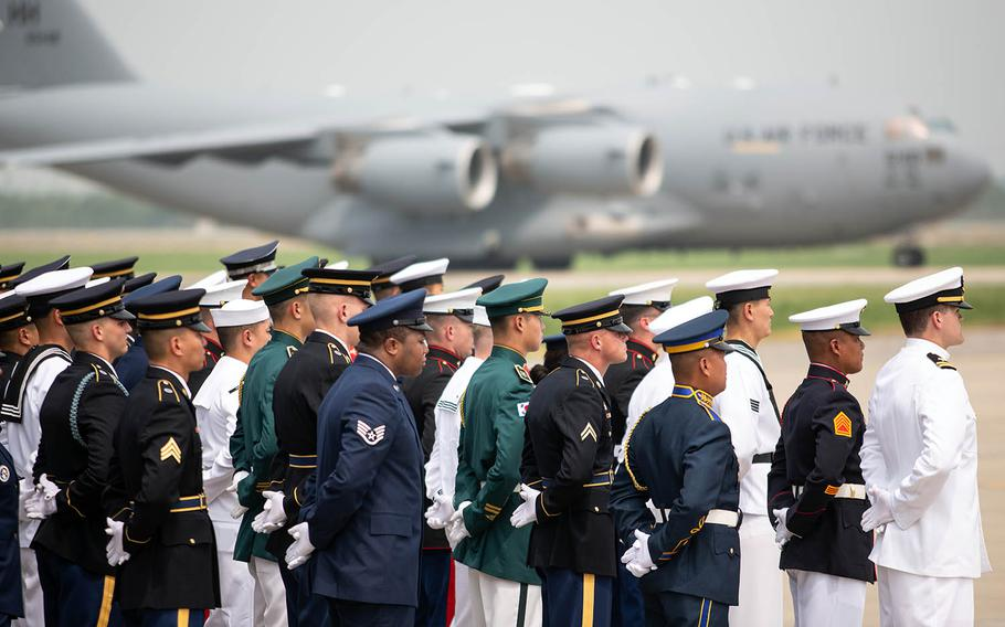 Honor Guard members wait as an aircraft carrying 55 sets of remains handed over by North Korea arrives at Osan Air Base, South Korea, Friday, July 27, 2018.