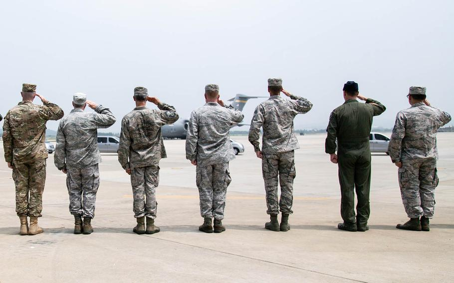 Servicemembers at Osan Air Base, South Korea, salute an aircraft carrying remains repatriated from the North, Friday, July 27, 2018.