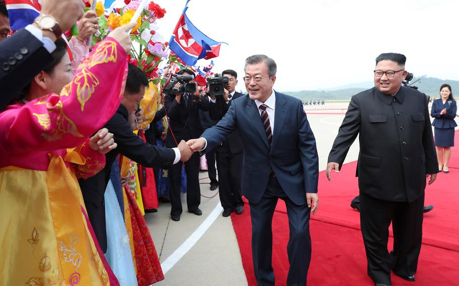 South Korean president Moon Jae-in (left) and North Korean leader Kim Jong Un greet North Korean citizens on Sept. 18, 2018.