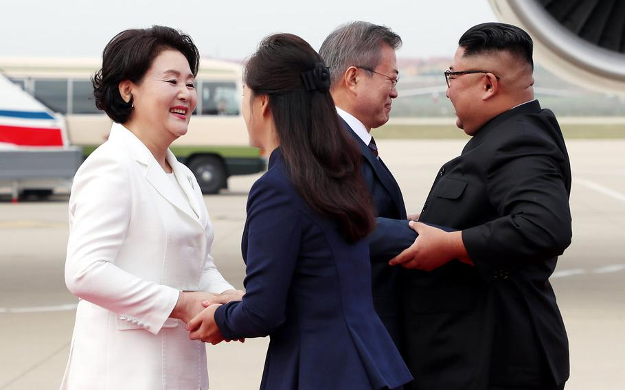 South Korean president Moon Jae-in (left) and his wife, Kim Jung-sook, greet North Korean leader Kim Jong Un and his wife, Ri Sol-ju, on a tarmac in North Korea on Sept. 18, 2018.