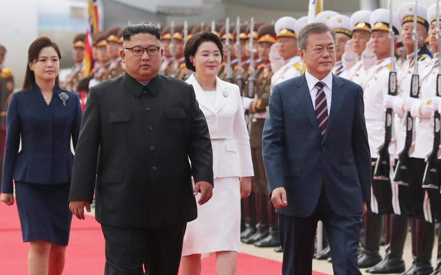 South Korean president Moon Jae-in (right) and his wife, Kim Jung-sook, walk with North Korean leader Kim Jong Un and his wife, Ri Sol-ju, on a tarmac in North Korea on Sept. 18, 2018.