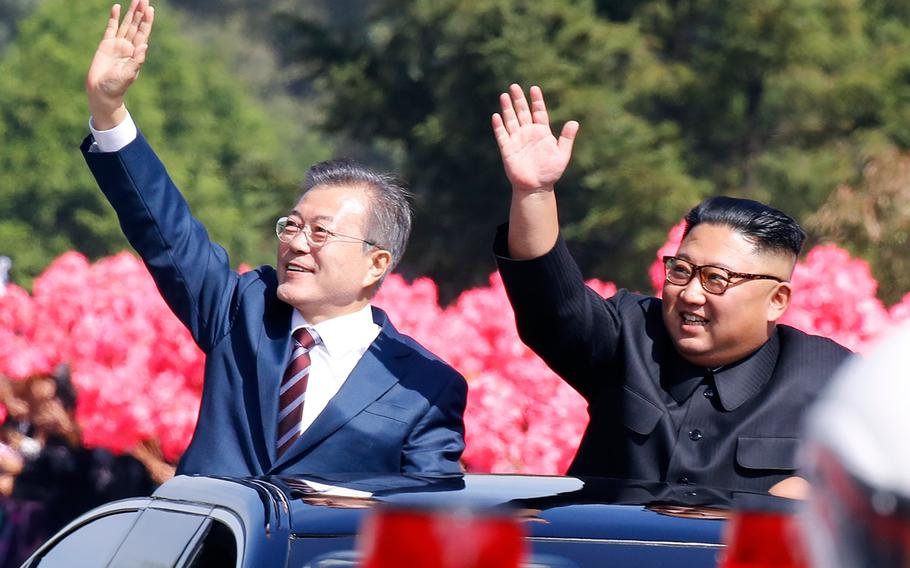 South Korean president Moon Jae-in (left) and North Korean leader Kim Jong Un wave to crowds during a procession in Pyongyang, North Korea on Sept. 18, 2018.