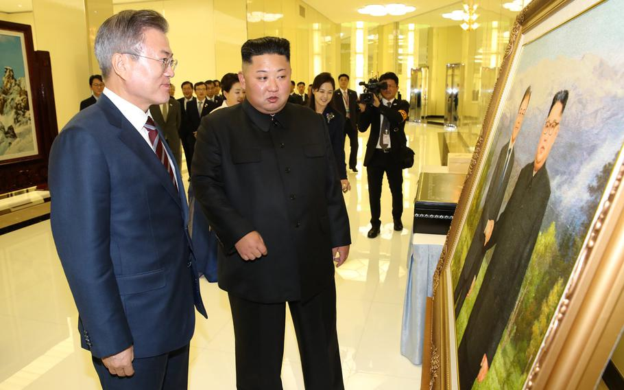 South Korean president Moon Jae-in (left) and North Korean leader Kim Jong Un examine an oil painting of the two men, given as a gift to South Korea by Kim, in Pyongyang, North Korea on Sept. 18, 2018.