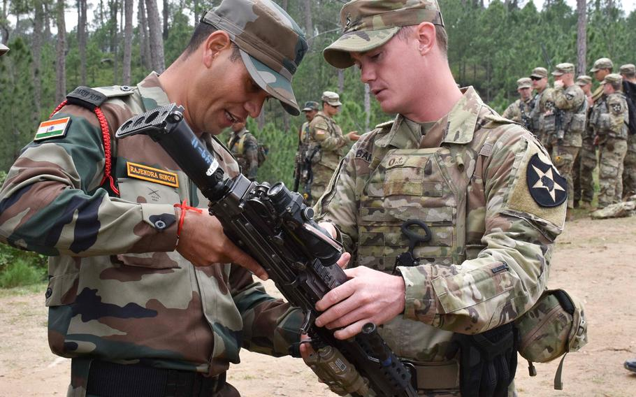 A soldier with U.S. Army's 1st Battalion, 23rd Infantry Regiment, talks about an M249 Squad Automatic Weapon with a soldier from the Indian army's 99th Mountain Brigade Sept. 24, 2018, at Chaubattia Military Station, India, during the Yudh Abhyas exercise.