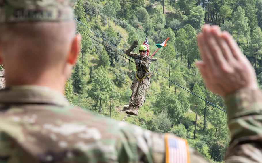 Spc. Sierra Hill, 1-2 Stryker Brigade Combat Team, takes the oath of enlistment on a zipline at Chaubattia Military Station, India, Sept. 25, 2018.