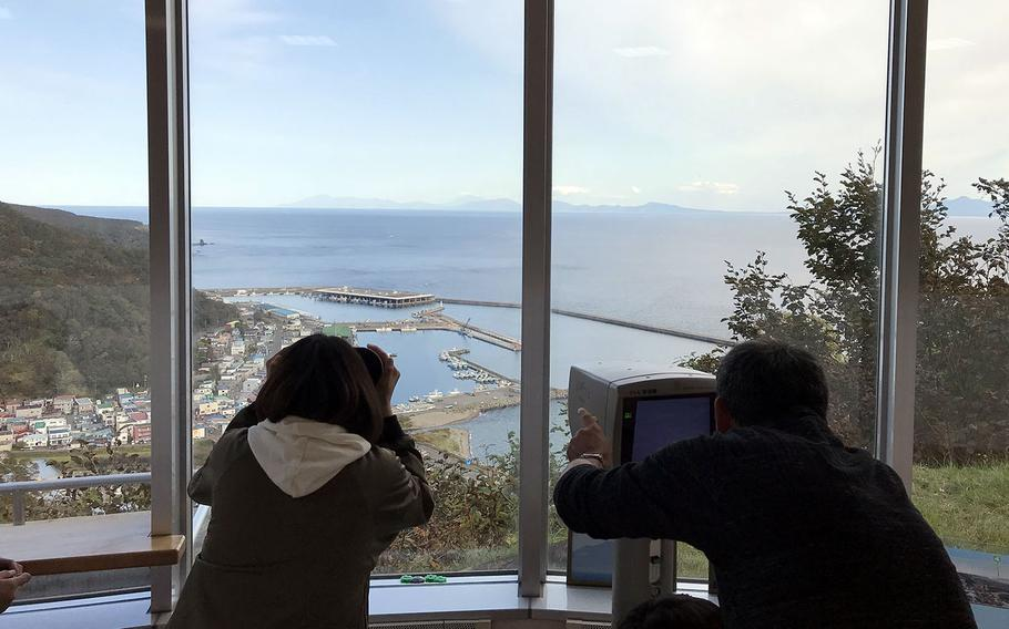 Visitors check out the Russian-held Kunashiri Island from an observatory on the northern Japanese island of Hokkaido.