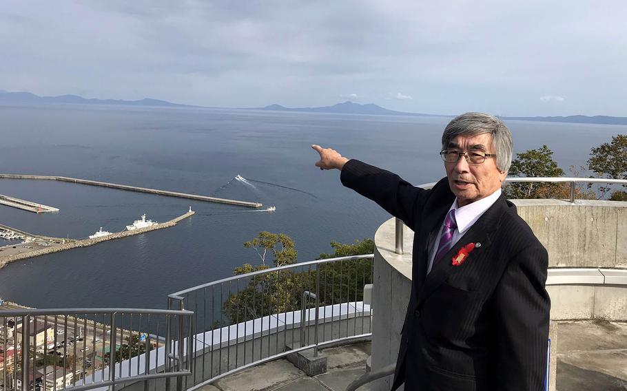 Kimio Waki points toward the island where he grew up from a lookout on Hokkaido's Shiretoko Peninsula, Wednesday, Oct. 10, 2018.
