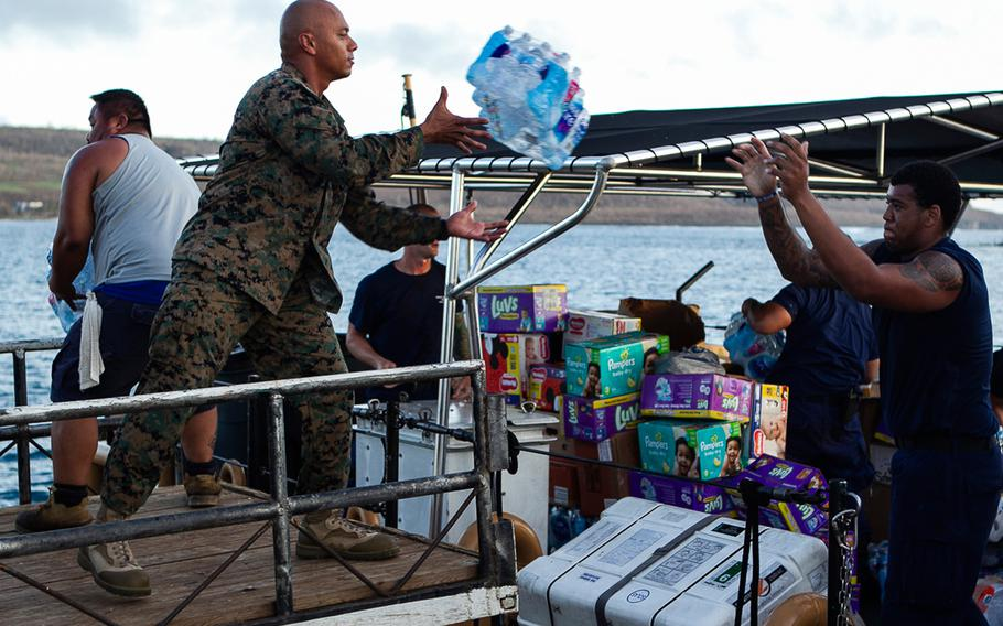 Gunnery Sgt. Angel Ignacio, the battalion gunnery sergeant with Combat Logistics Battalion 31, catches a package of bottled water from a Coast Guard member aboard the U.S. Coast Guard cutter Washington while delivering food and supplies to citizens of Tinian, Oct. 29, 2018.