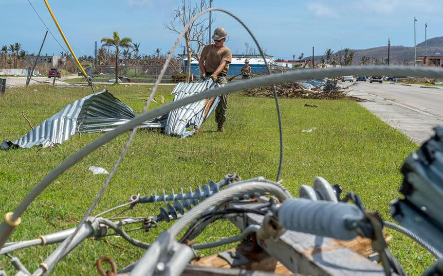 A sailor assigned to the U.S. Navy's Naval Mobile Construction Battalion 1 removes debris from a road on Tinian Island during recovery operations Nov. 1, 2018, following Super Typhoon Yutu.