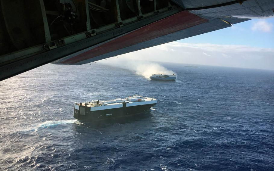 A Coast Guard C-130 flies over the 650-foot Sincerity Ace on fire 1,800 nautical miles northwest of Oahu in the Pacific Ocean, Dec. 31, 2018, and drops supplies to the bulk carrier Genco Augustus also responding to the emergency.