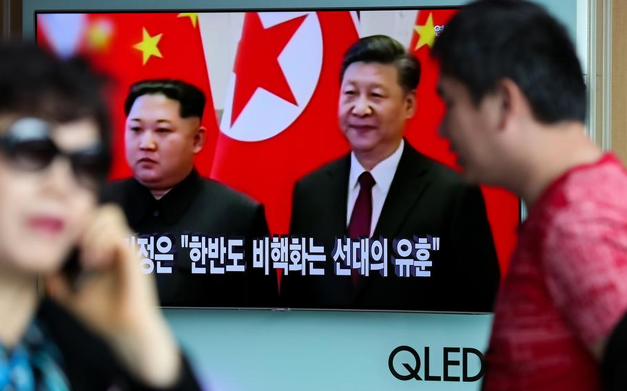 Pedestrians in Seoul, South Korea, walk past a television screen with North Korean Leader Kim Jong Un during a meeting with China's president Xi Jinping on March 28, 2018. A senior U.N. envoy said talks with North Korea should include a discussion on human rights.