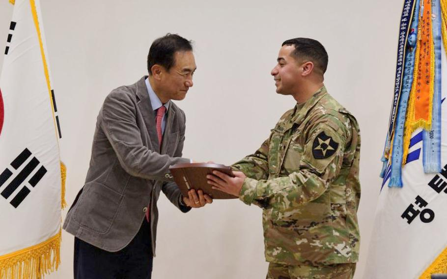 Pyeongtaek Mayor Jung Jang-seon presents a plaque of appreciation to Army Spc. Jonathan Roman Rios in Pyeongtaek, South Korea, Thursday, March 28, 2019.