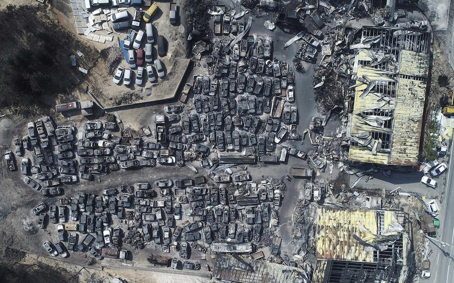 This aerial photo shows burnt vehicles filling a junkyard after being hit by a massive forest fire in Sokcho, South Korea, Friday, April 5, 2019.