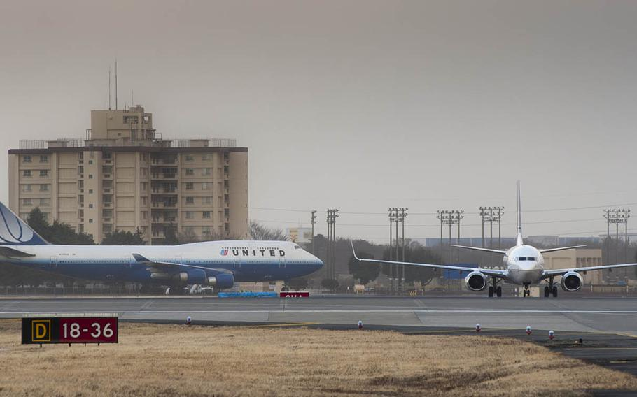 Commercial aircraft arrive at Yokota Air Base in western Tokyo after being diverted from Narita International Airport following a major earthquake and tsunami on March 11, 2011.
