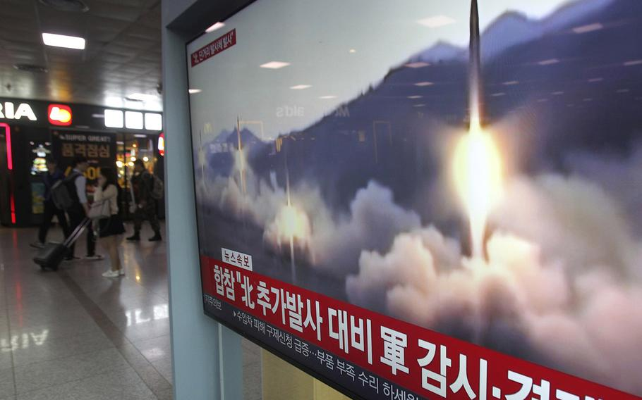 """A TV screen shows a file footage of North Korea's missile launch during a news program at the Seoul Railway Station in Seoul, South Korea, Saturday, May 4, 2019. The signs read: """"Strengthening military alertness."""""""