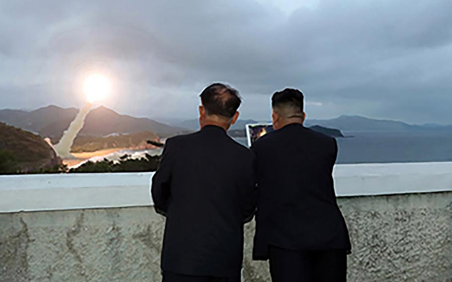 North Korean leader Kim Jong Un, right, watches a missile launch in this photo released by the Korean Central News Agency on Aug. 11, 2019.