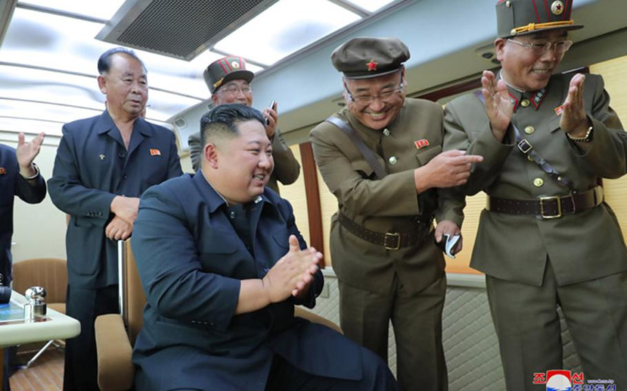 """This undated photo, released by the state-run Korean Central News Agency on Aug. 17, 2019, shows North Korean leader Kim Jong Un observing the test-firing of a """"new weapon,"""" according to KCNA."""