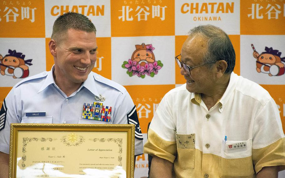 Master Sgt. Roger Halle, left, receives a letter of appreciation from Chatan Mayor Masaharu Noguni at Chatan Town Hall, Okinawa, Japan, on Monday, Aug. 19, 2019.
