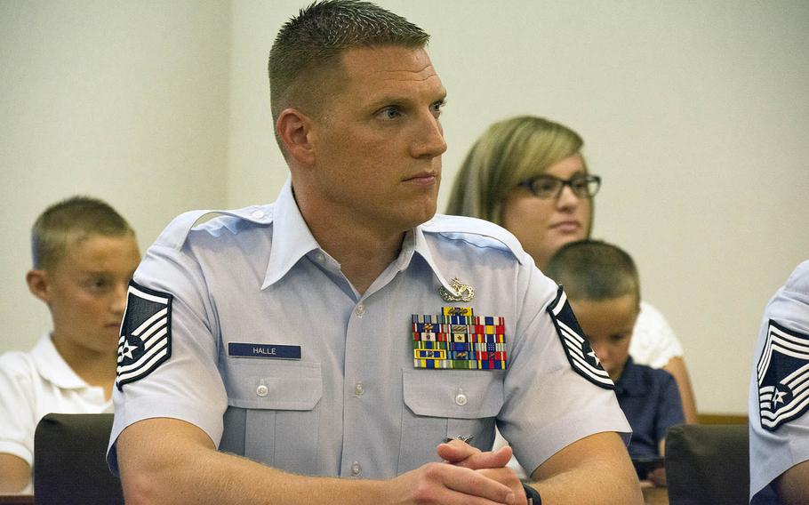 Master Sgt. Roger Halle, of Kadena Air Base, accompanied by his wife, Stephanie Halle, and two of heir sons, awaits recognition from the mayor at a town hall ceremony at Chatan, Okinawa, Japan, on Monday, Aug. 19, 2019.