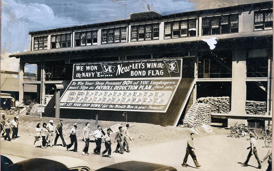 Workers file past Building 1, festooned for a war bonds drive, at the Pearl Harbor Naval Shipyard, in this undated photo taken during World War II.