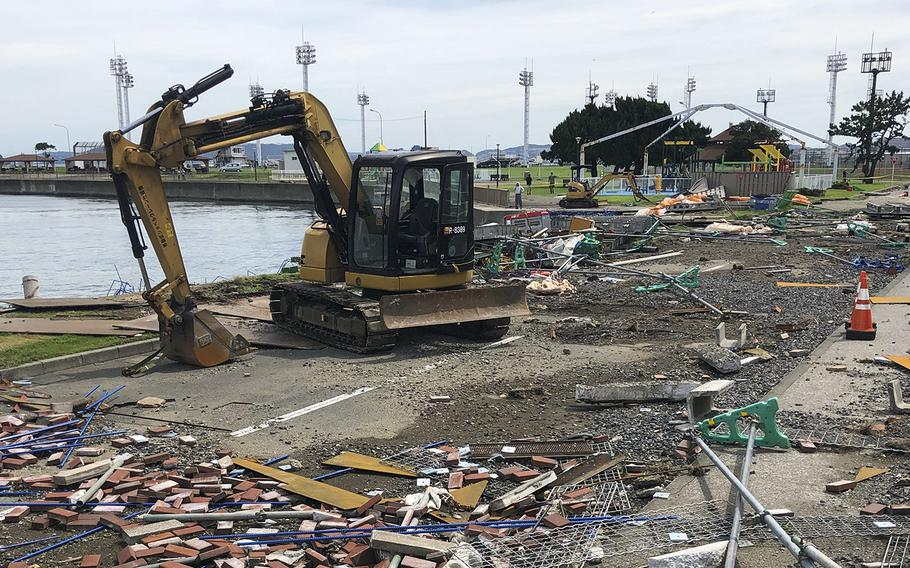 Workers clear debris from Typhoon Faxai at Yokosuka Naval Base, Japan, Monday. Sept. 9, 2019.