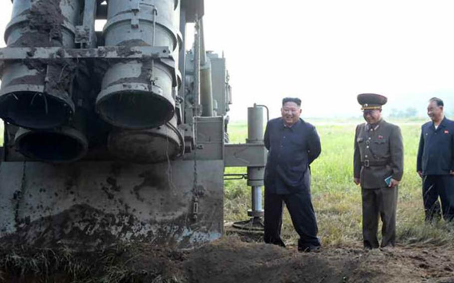 North Korean leader Kim Jong Un stands near a mobile launcher in this undated photo released by the state-run Rodong Sinmun newspaper, Wednesday, Sept. 11, 2019.