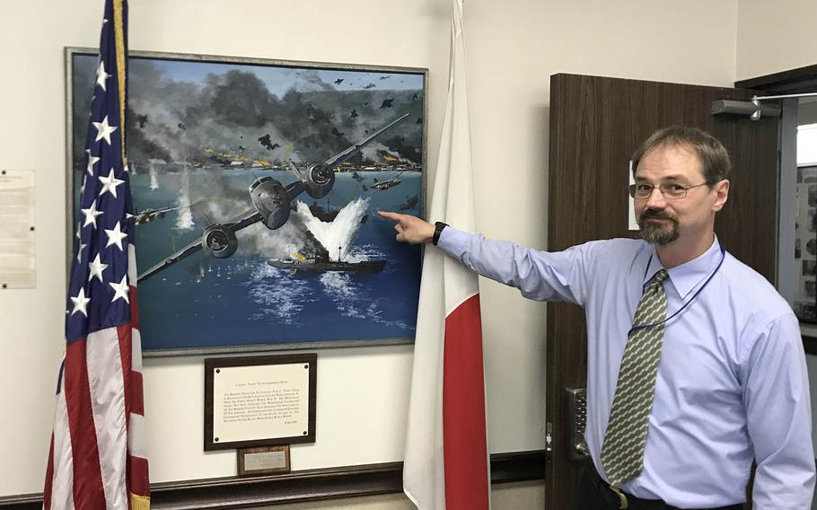 """Greg Mattson, the 5th Air Force historian, shows off a painting in the unit headquarters that depicts a World War II exploit of Col. Paul Irvin """"Pappy"""" Gunn on Sept. 11, 2019."""