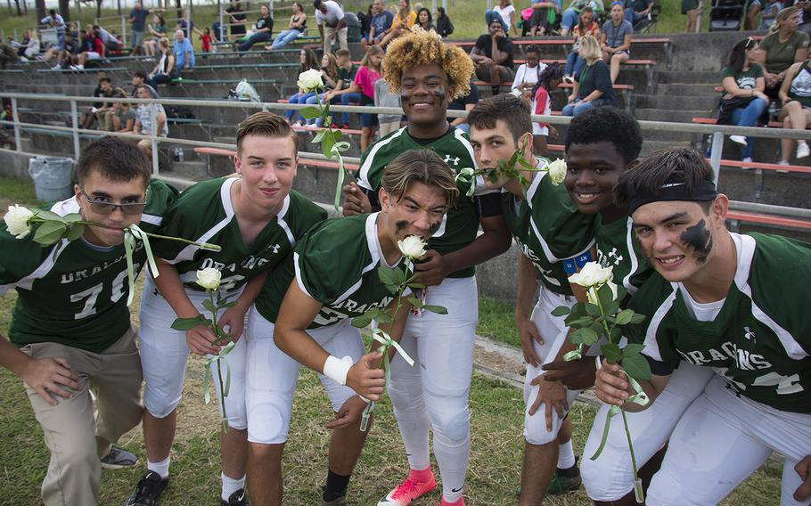 Senior football players from Kubasaki High School clown around for the camera before giving flowers to their parents ahead of a matchup with the Camp Humphreys Blackhawks at Camp Foster, Okinawa, Friday, Oct. 25, 2019.