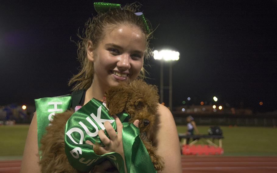 A  Kubasaki High School cheerleader poses with a pooch during a matchup with Camp Humphreys at Mike Petty Stadium on Camp Foster, Okinawa, Friday, Oct. 25, 2019.