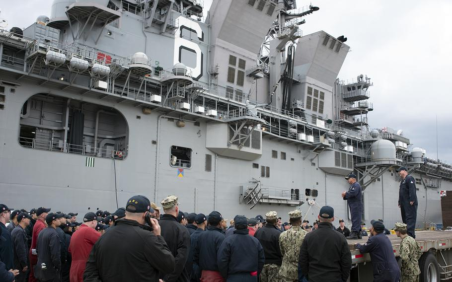 An officer assigned to the amphibious assault ship USS America speaks to sailors after arriving at Sasebo Naval Base, Japan, Friday, Dec. 6, 2019.