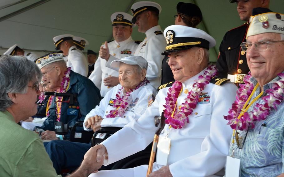 Lou Conter, shaking hands, sits with other veteran survivors of the Japanese surprise attack on Oahu before the beginning of a ceremony Dec. 7, 2019, at the Pearl Harbor National Memorial that marked the event.