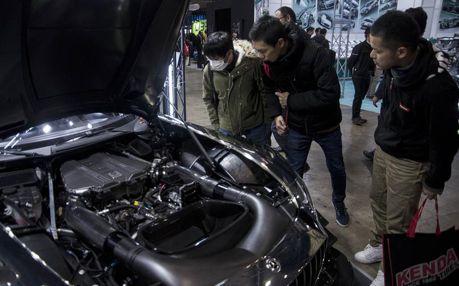 Auto enthusiasts check out the engine bay of a Mercedes sports car during Tokyo Auto Salon 2020 in Chiba, Japan, Friday, Jan. 10, 2020.