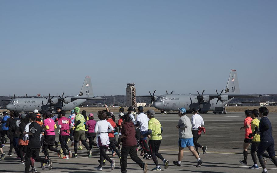 Runners pass C-130J Super Hercules aircraft from the 374th Airlift Wing during the 39th annual Yokota Striders Frostbite road race at Yokota Air Base, Japan, Sunday, Jan. 19, 2020.