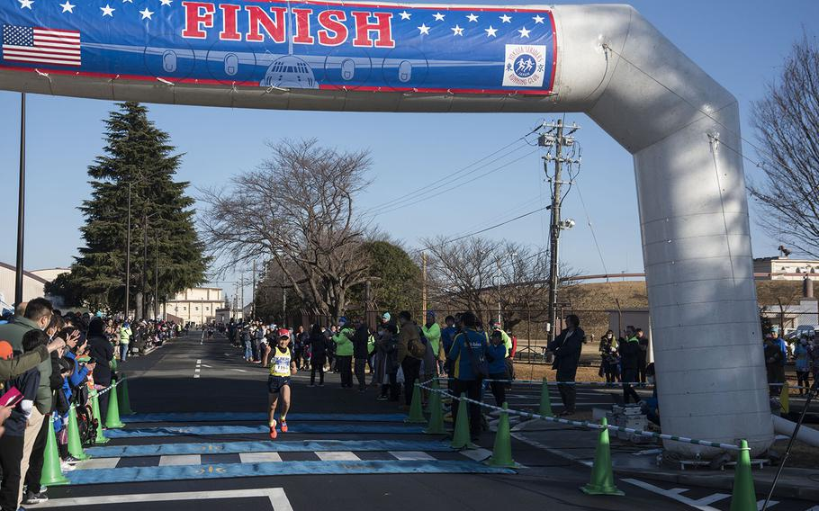 A young athlete crosses the finish line during the 39th annual Yokota Striders Frostbite road race at Yokota Air Base, Japan, Sunday, Jan. 19, 2020.