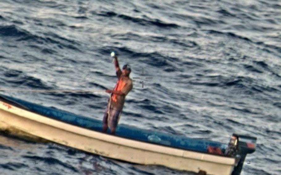 A fisherman stranded for five days in the Pacific Ocean signals to the crew of a Navy P-8A Poseidon about 600 nautical miles from Guam, Friday, Jan. 17, 2020.