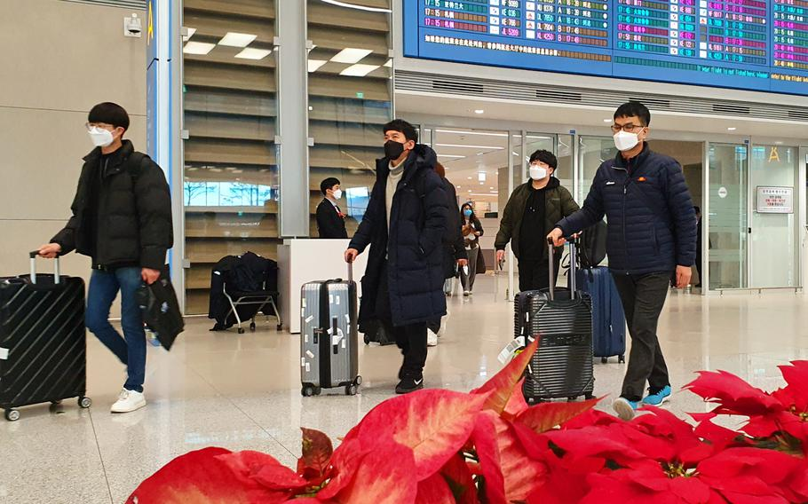 Airplane passengers exit an arrival gate wearing masks at Incheon International Airport, South Korea, Monday, Feb. 3, 2020.