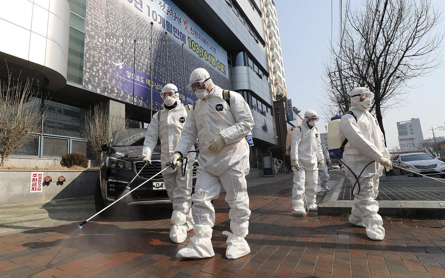 Workers wearing protective gears spray disinfectant against the new coronavirus in front of a church in Daegu, South Korea, Thursday, Feb. 20, 2020.
