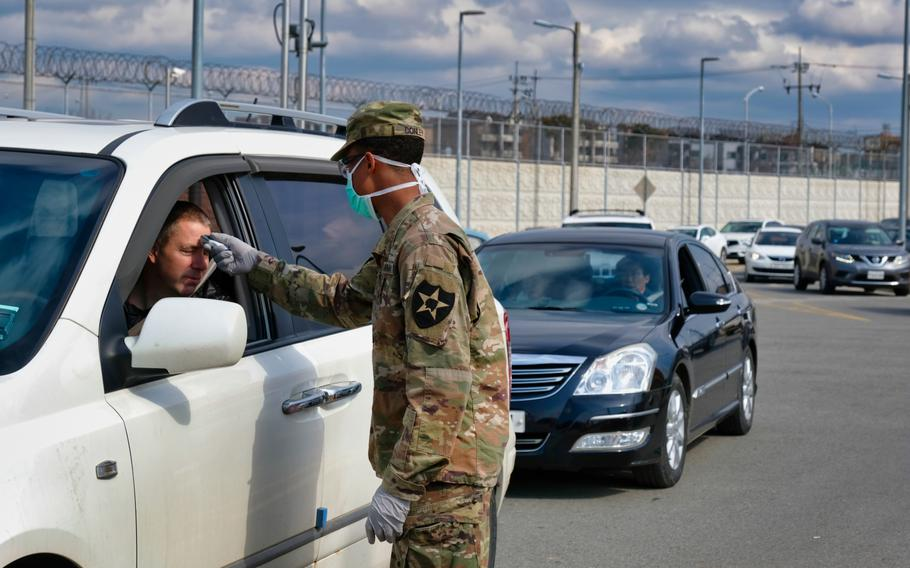 A 2nd Infantry Division soldier checks for a temperature as dozens of vehicles line up to enter the Dongchang-ri gate at Camp Humphreys, South Korea, Wednesday, Feb. 26, 2020.
