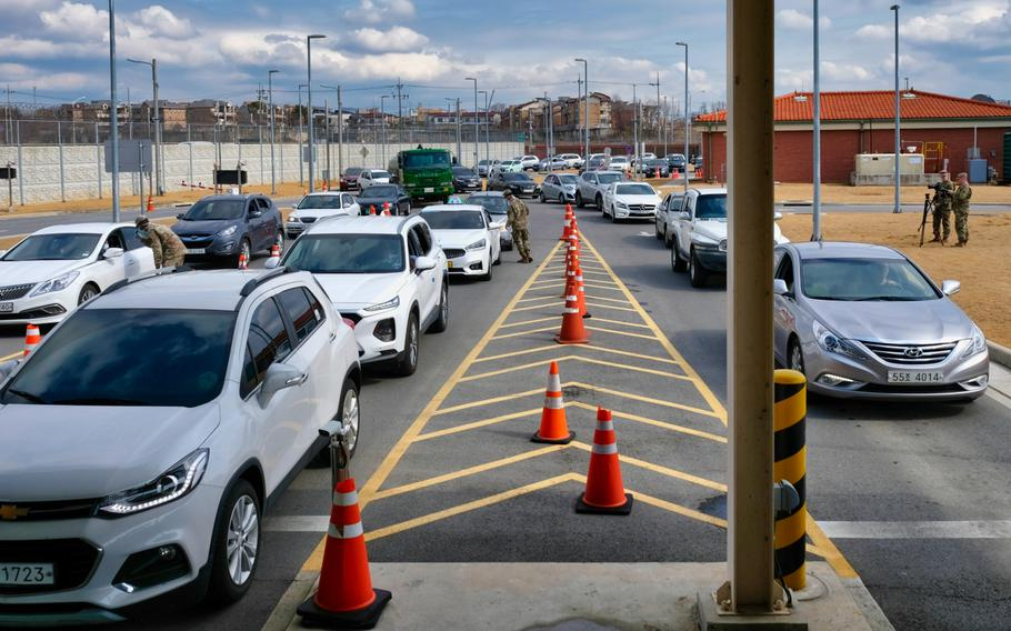 A stream of vehicles wait to enter the Dongchang-ri gate at Camp Humphreys, South Korea, Wednesday, Feb. 26, 2020, as soldiers screen visitors for the new coronavirus.