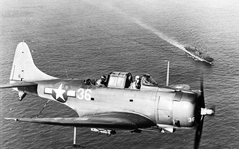 An undated close-up photo from World War II shows the two-man cockpit crew of an SBD Dauntless flying over the USS Enterprise.