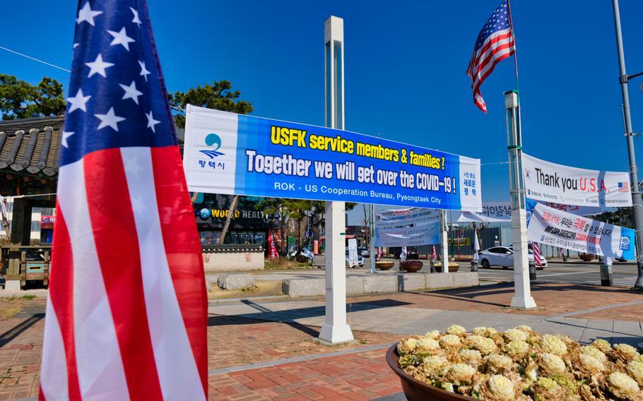 American flags wave alongside coronavirus banners outside Camp Humphreys, South Korea, Monday, March 16, 2020.
