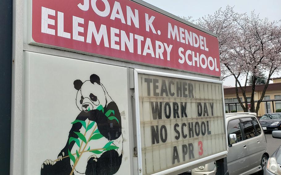 A sign outside Joan K. Mendel Elementary School announces an upcoming teacher work day at Yokota Air Base, Japan, Tuesday, March 31, 2020.