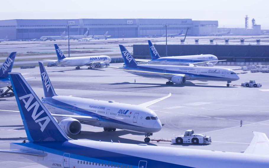 Commercial jets are pulled to their gates at Haneda International Airport in Tokyo, March 18, 2020.