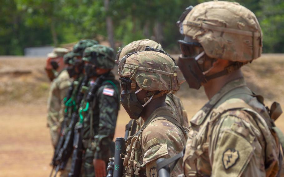 Thai and U.S. soldiers, wearing masks to reduce the risk of coronavirus infection, stand at attention at Krabi, Thailand, during the opening ceremony of the Hanuman Guardian exercise, March 30, 2020.